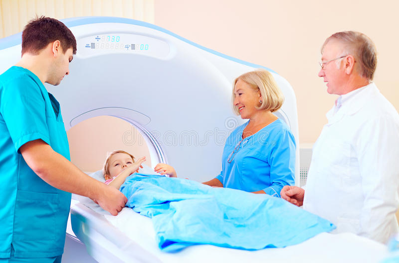 Little patient kid among medical staff ready for ct scanning. Little patient kid among medical staff is ready for ct scanning royalty free stock image