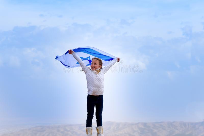 Little patriot jewish girl with the flag of Israel on blue sky background. royalty free stock image
