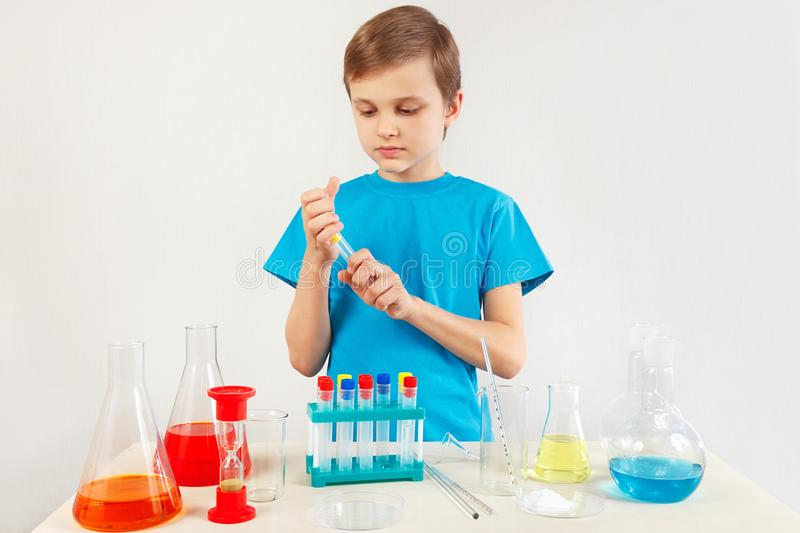 Little pensive boy doing chemical experiments in laboratory. Little pensive boy doing chemical experiments in the laboratory stock photos