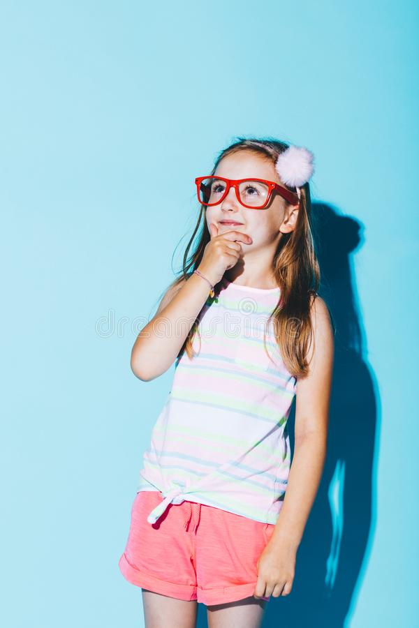 Little pensive girl in red glasses rubbing her chin stock photography