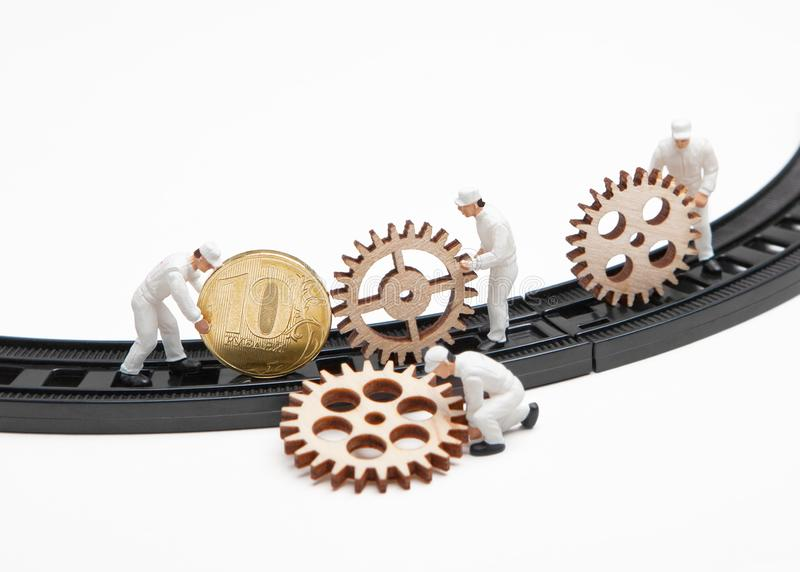 Little people dolls with gears and coin on rails. On a white background royalty free stock photos