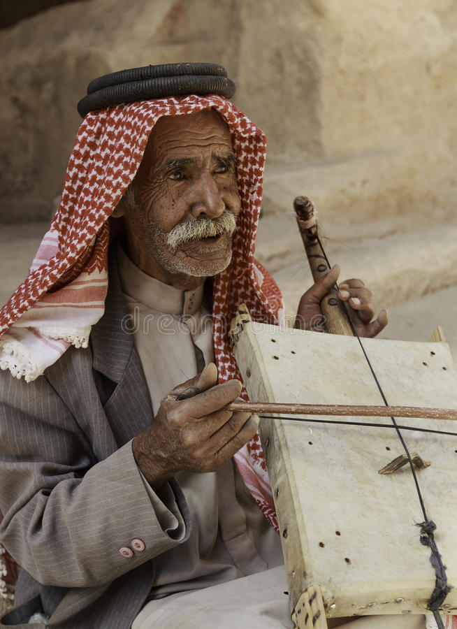 Little Petra, Jordan – June 20, 2017: Old Bedouin man or Arab man in traditional outfit, playing his musical instrument . stock image