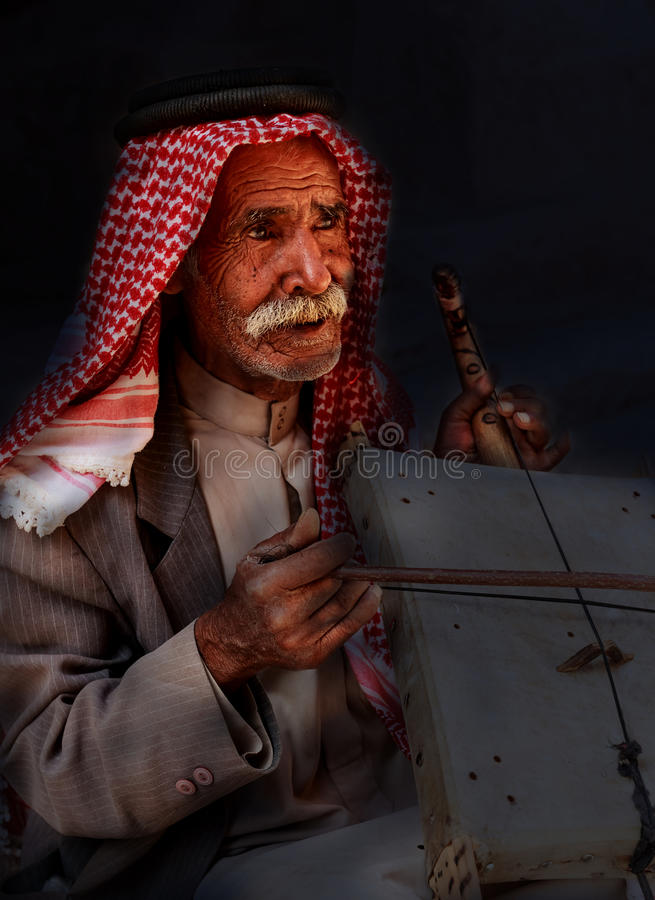 Little Petra, Jordan – June 20, 2017:Old Bedouin man or Arab man in traditional outfit, playing his musical instrument . stock photo