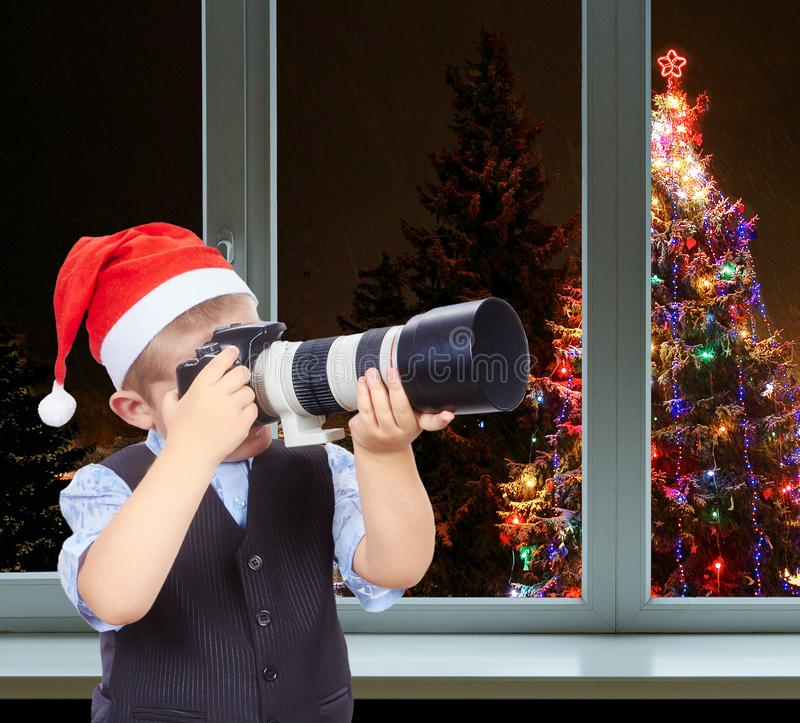 Little photographer in cap of Santa Claus on a background decorated Christmas tree outside the window royalty free stock photo