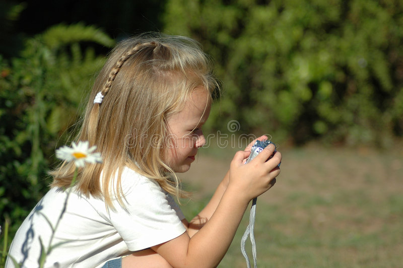 Little photographer girl. A beautiful little blond caucasian girl child photographer taking photographs of flowers with her own camera in the garden outside stock photography