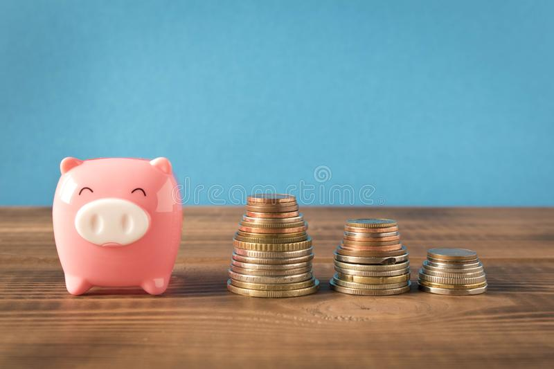 Little piggy Bank and a few stack coins on the wooden table. Close up. The concept of saving money royalty free stock photo