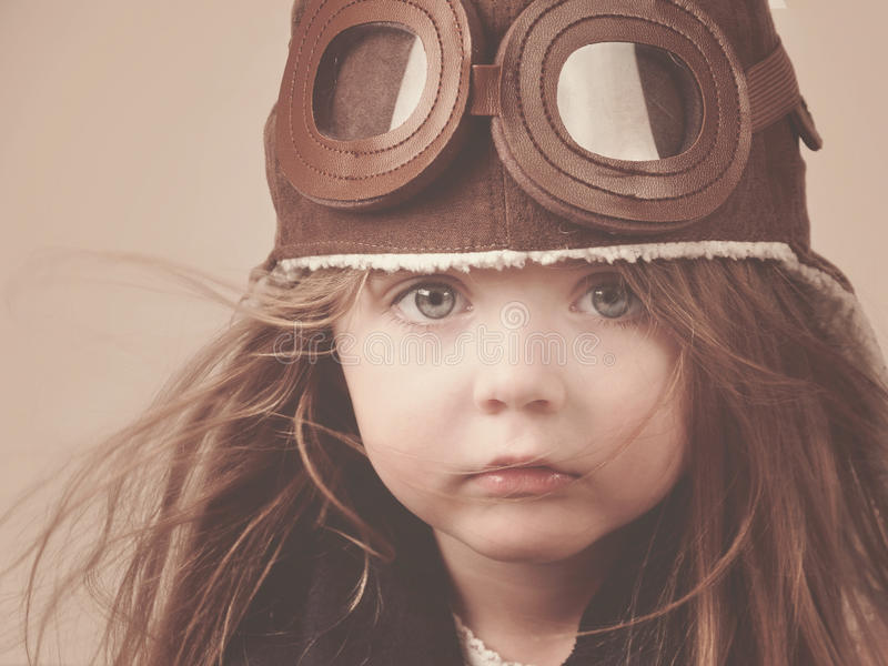 Little Pilot Girl with Hat. A little girl is wearing a pilot hat with goggles with an antique concept for career or imagination message stock photo