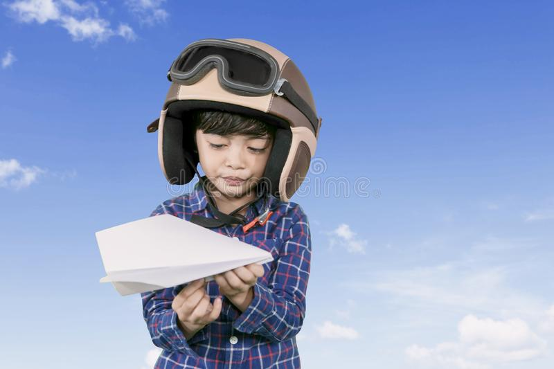 Little pilot holding a paper plane at outdoors. Picture of little male pilot wearing helmet while holding a paper plane with blue sky background royalty free stock images