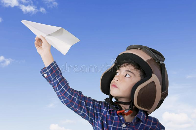 Little pilot playing a paper plane. Picture of a little male pilot wearing helmet while playing a paper plane with blue sky background royalty free stock photos