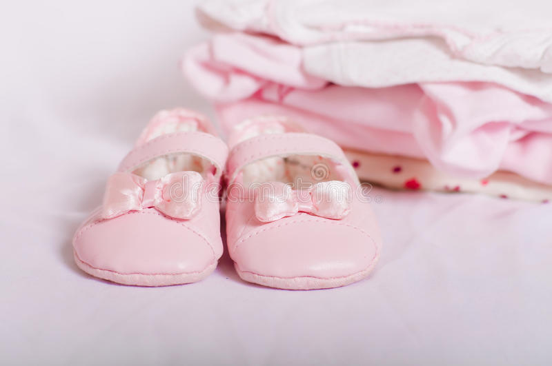 Little pink baby shoes and baby clothes. Pink baby shoes and baby clothes stock photography