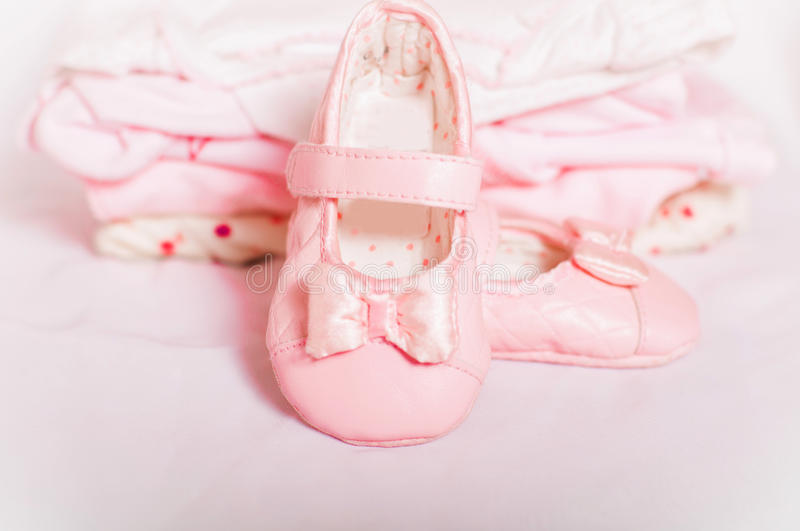 Little pink baby shoes and baby clothes. Pink baby shoes and baby clothes royalty free stock photography