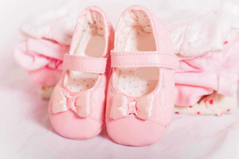 Little pink baby shoes and baby clothes. Pink baby shoes and baby clothes royalty free stock image