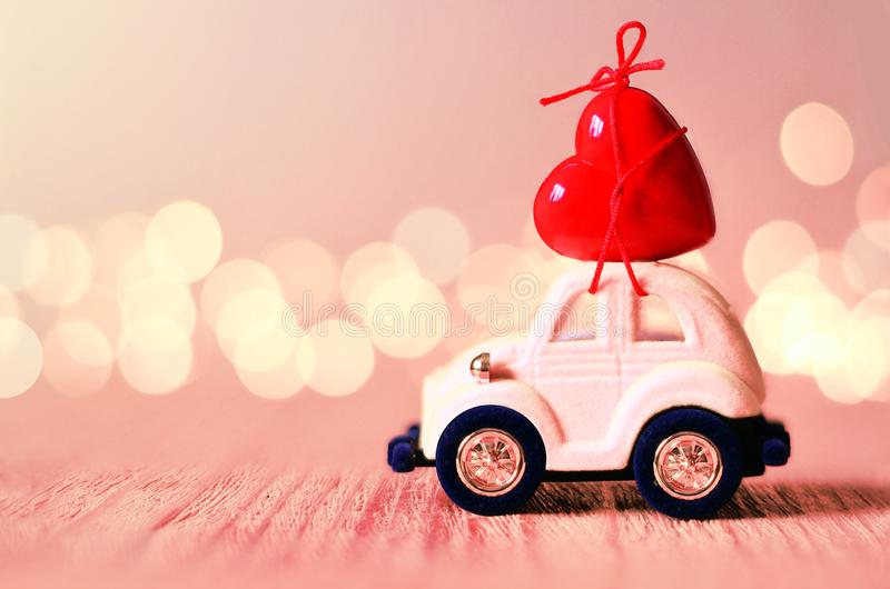 Little pink beetle car carries a heart. The concept of Valentine Day stock photography