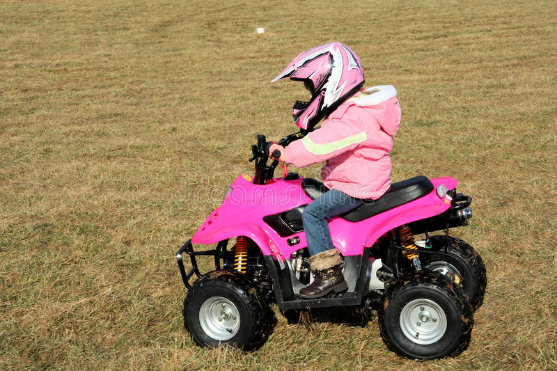 Little Pink Four Wheeler Quad Girl 4. A little girl riding a pink four wheeler quad in her backyard royalty free stock image