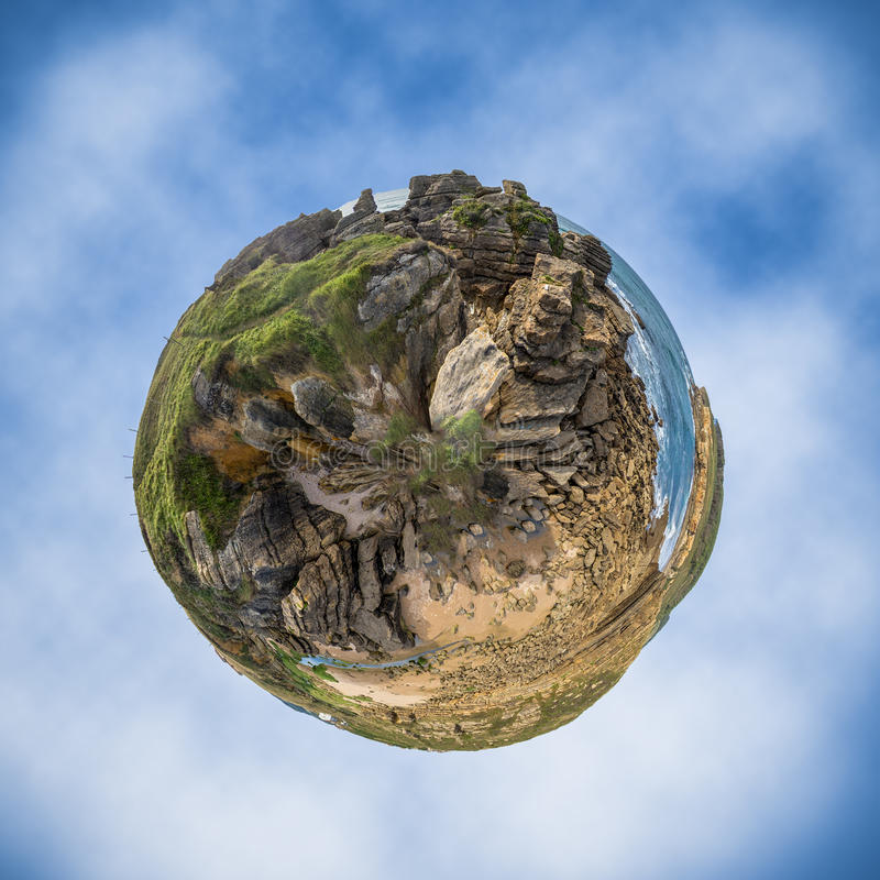 Little planet of grass, rocks and ocean. Little planet build f grass, rocks and ocean with a beach on a blue cloudy background stock image