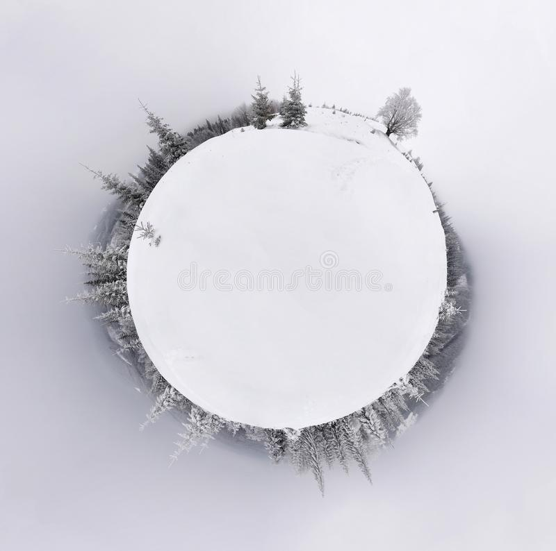 Little planet panorama of snowy hills montains landscape with forest. royalty free stock photography