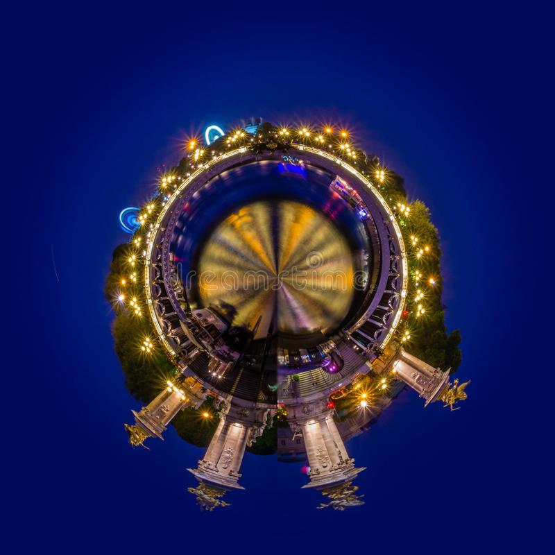 Little planet view of Alexander II bridge in Paris at night with big wheels in the background royalty free stock photography