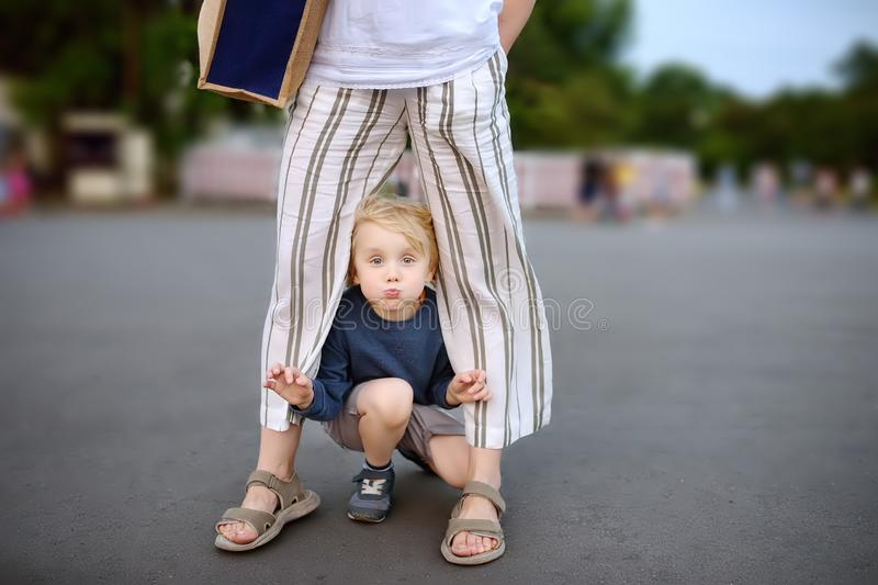 Little playful boy having fun during walking with his mother. Child fooling around warm summer evening in public park. Hyperactive kid royalty free stock photos