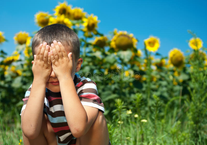 Little plays hide-and-seek stock photography
