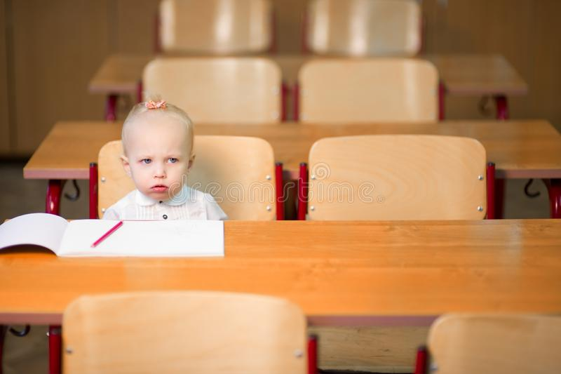 Little preschool girl sits at her desk and looks very upset. Little preschool girl sits at her desk in the classroom and looks very upset royalty free stock photo