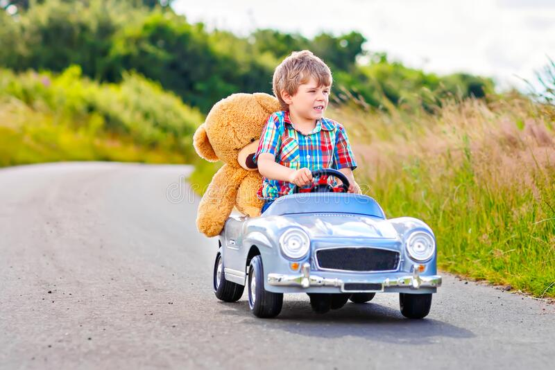 Little preschool kid boy driving big toy car and having fun with playing with his plush toy bear, outdoors. Child royalty free stock images