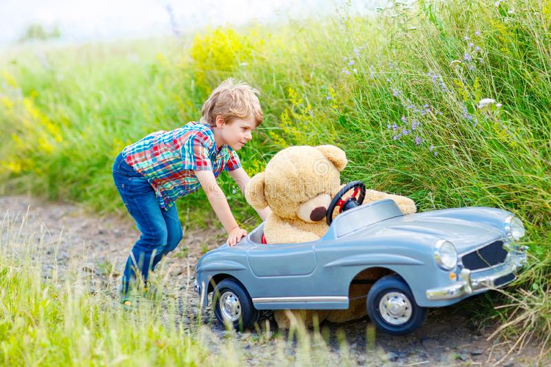 Little kid boy driving big toy car with a bear, outdoors. stock photos