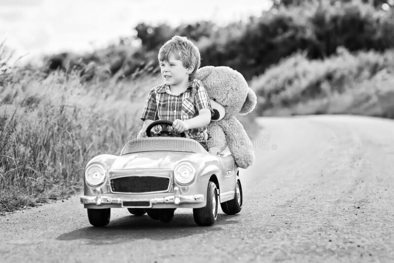 Little preschool kid boy driving big toy car and having fun with playing with his plush toy bear, outdoors. Child stock photos