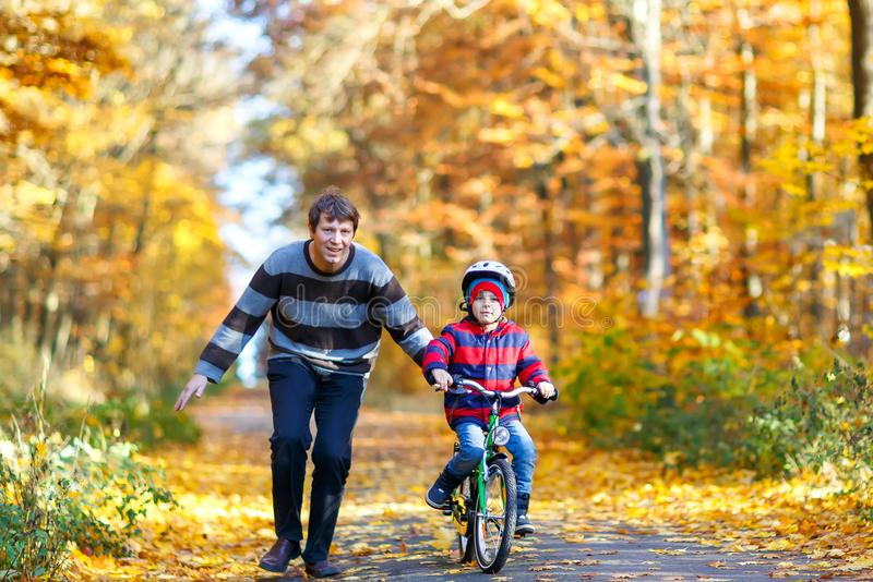 Little kid boy and his father in autumn park with a bicycle. Dad teaching his son biking. Little preschool kid boy and his father in autumn park with a bicycle stock photos