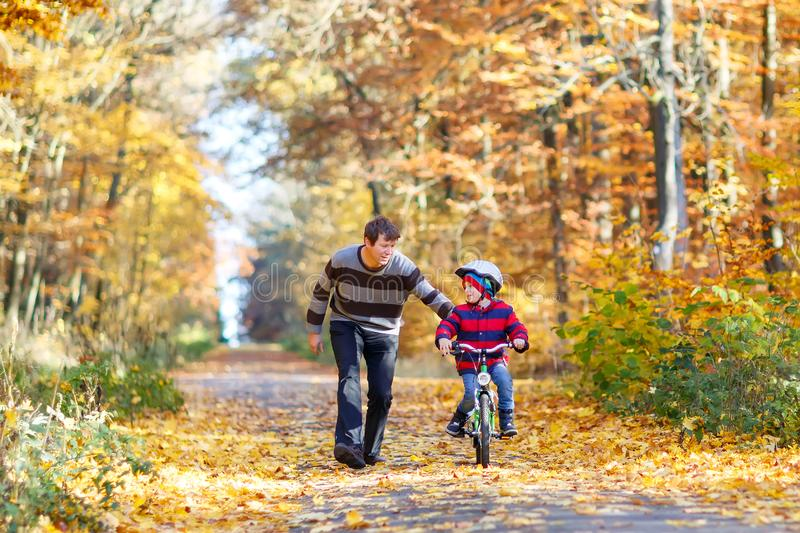 Little kid boy and his father in autumn park with a bicycle. Dad teaching his son biking. Little preschool kid boy and his father in autumn park with a bicycle royalty free stock photo
