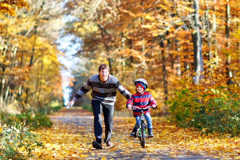Little preschool kid boy and his father in autumn park with a bicycle. Dad teaching his son biking. Active family. Leisure. Child with helmet on bike. Safety stock images