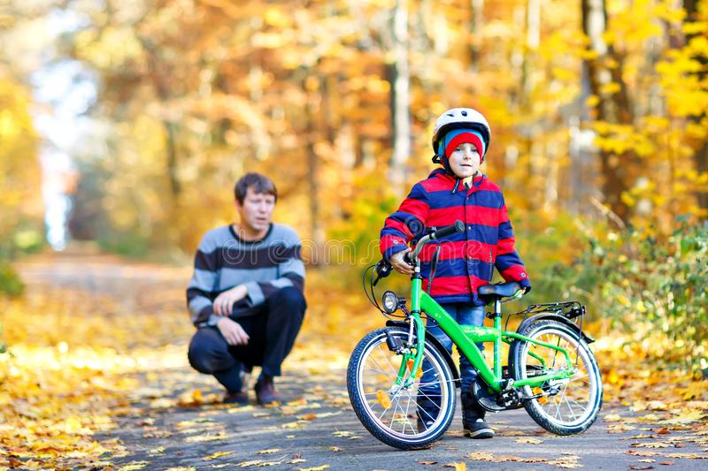 Little kid boy and his father in autumn park with a bicycle. Dad teaching his son biking. Little preschool kid boy and his father in autumn park with a bicycle stock images