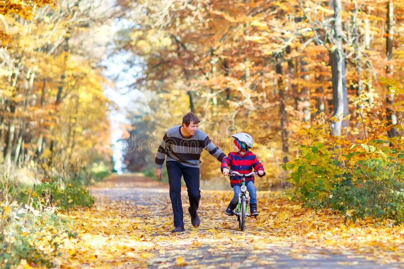 Little preschool kid boy and his father in autumn park with a bicycle. Dad teaching his son biking. Active family. Leisure. Child with helmet on bike. Safety royalty free stock photos