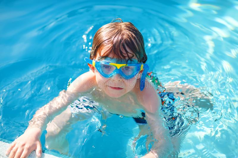 Little preschool kid boy making swim competition sport. Kid with swimming goggles reaching edge of the pool . Child. Having fun in an swimming pool. Active royalty free stock photography