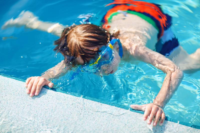 Little preschool kid boy making swim competition sport. Kid with swimming goggles reaching edge of the pool . Child. Having fun in an swimming pool. Active royalty free stock photo
