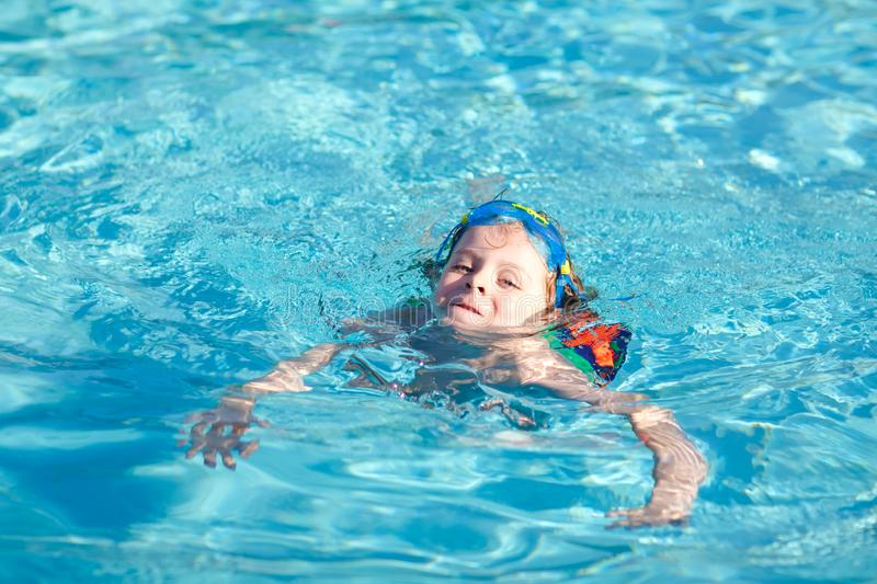 Little preschool kid boy making swim competition sport. Kid with swimming goggles reaching edge of the pool . Child. Having fun in an swimming pool. Active royalty free stock image
