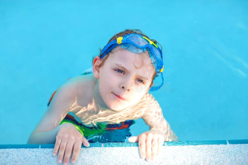 Little preschool kid boy making swim competition sport. Kid with swimming goggles reaching edge of the pool . Child. Having fun in an swimming pool. Active stock image