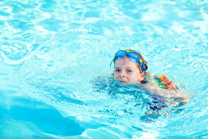 Little preschool kid boy making swim competition sport. Kid with swimming goggles reaching edge of the pool . Child. Having fun in an swimming pool. Active stock photos