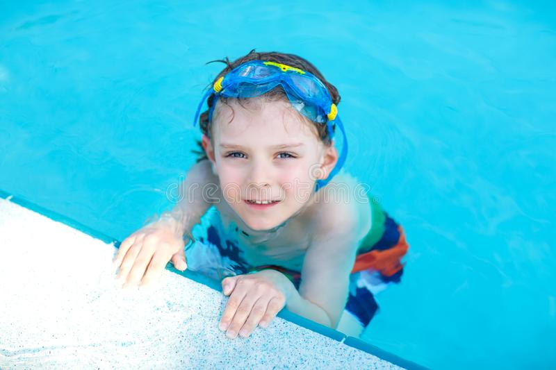 Little preschool kid boy making swim competition sport. Kid with swimming goggles reaching edge of the pool . Child. Having fun in an swimming pool. Active stock photo