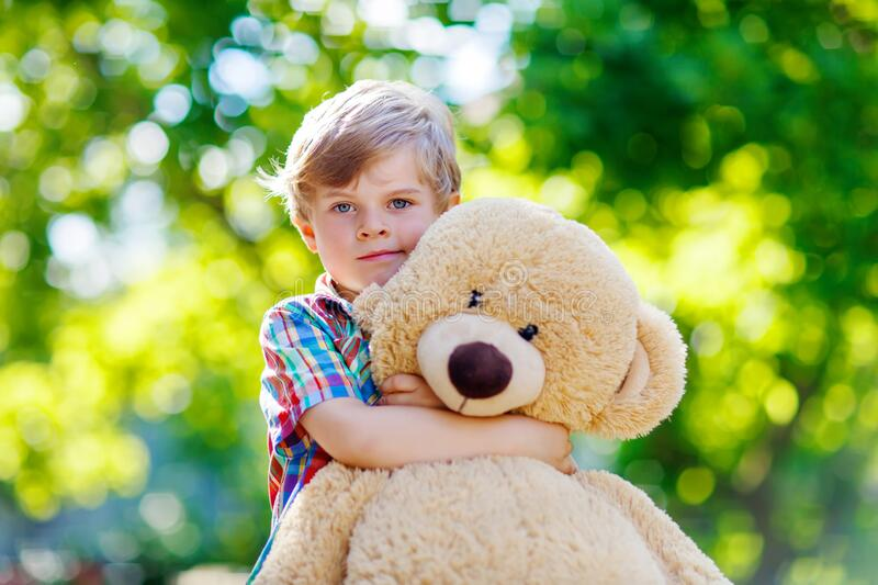 Little preschool kid boy playing with his big plush toy bear, outdoors. Child enjoying warm summer day in nature stock photography