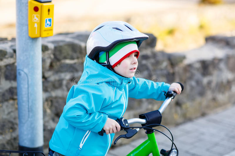 Little preschool kid boy riding with his first green bike. In the city. Happy child in colorful clothes standing and waiting near traffic lights. Active leisure stock photo