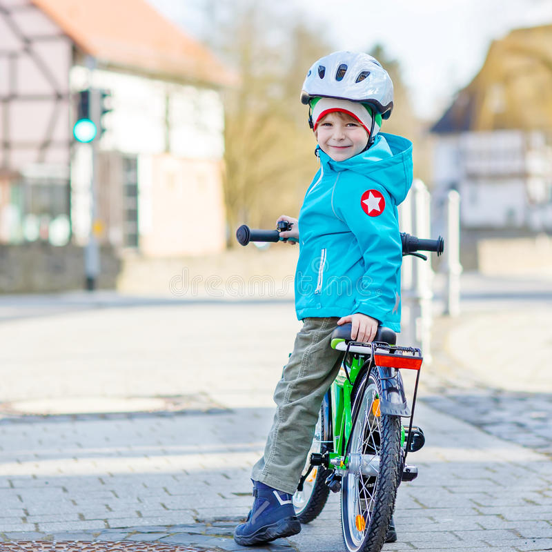Little preschool kid boy riding with his first green bike. Lovely preschool kid boy in helmet riding with his first green bike in the city. Happy child in royalty free stock photography