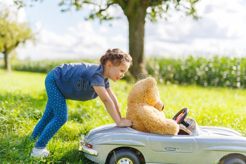 Little preschool kid girl driving big toy car and having fun with playing with big plush toy bear. Little preschool kid girl driving big vintage old toy car and royalty free stock photo