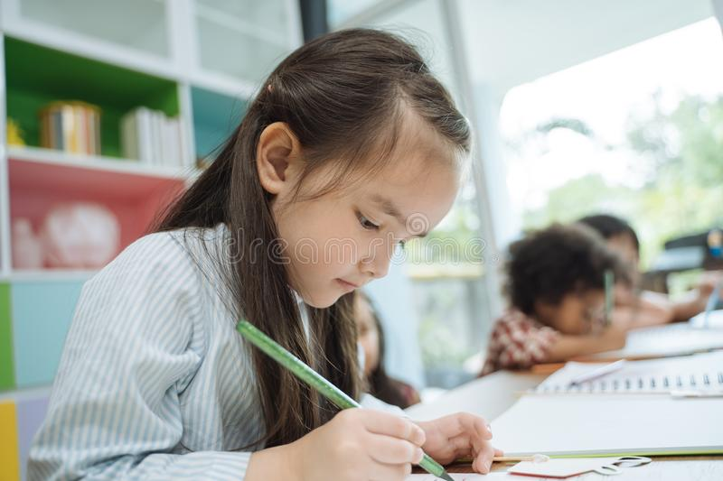 Little preschool kids drawing paper with color pencils . portrait of girl with friends education concept. royalty free stock images