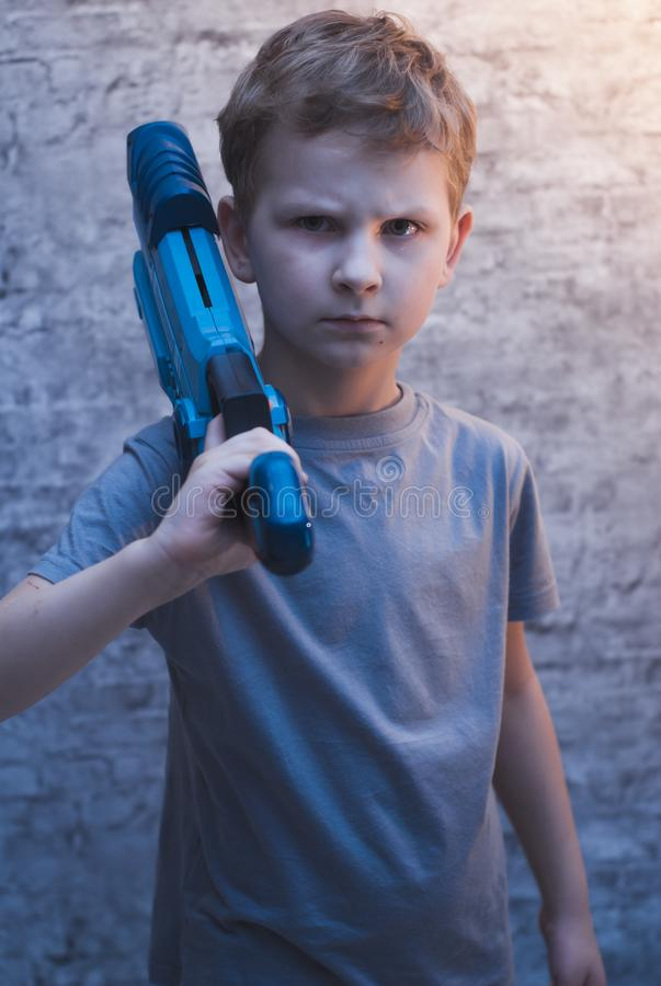 Little preschooler boy holding the Blaster with a dramatic face. Young actor with a toy gun royalty free stock photo