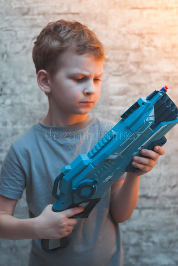 Little preschooler boy holding the Blaster with a dramatic face. Young actor with a toy gun stock photography