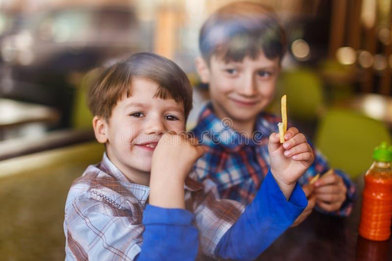 Little preschooler boys in fast food restaurant royalty free stock photo