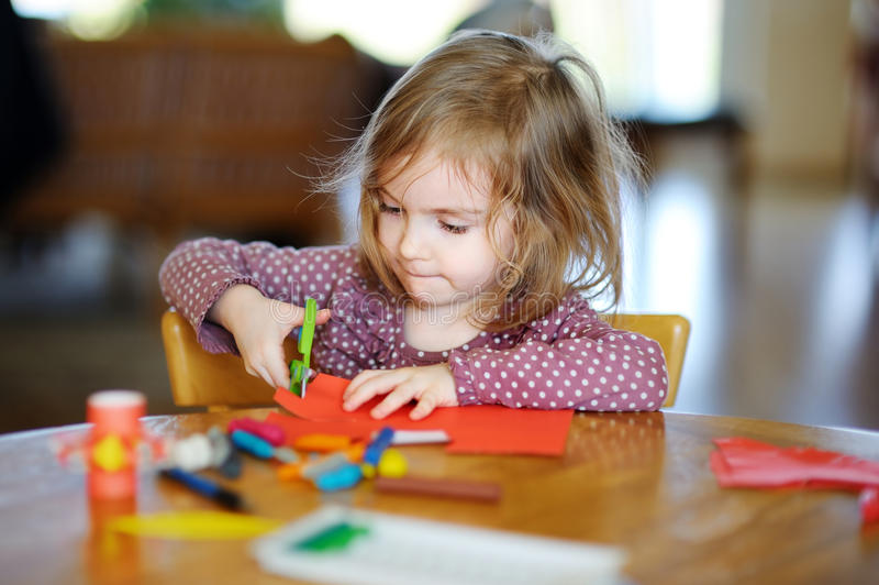 Little preschooler girl cutting paper royalty free stock images