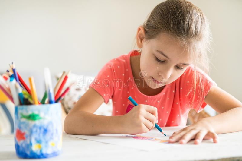 Little preschooler girl diligently drawing something with blue pencil royalty free stock photo