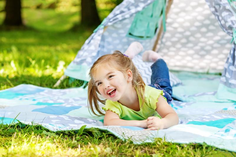 A little preschooler is lying on a blanket and laughing. Summer. stock photo