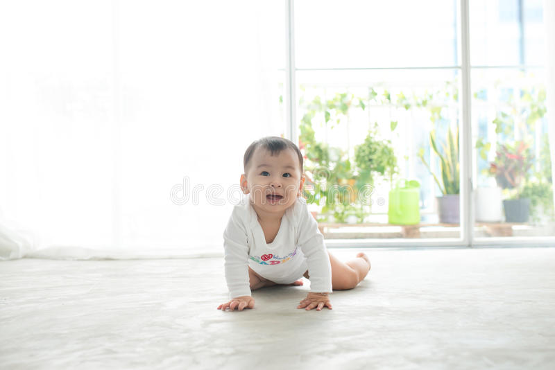 Little pretty baby girl crawling on the floor at home stock photo